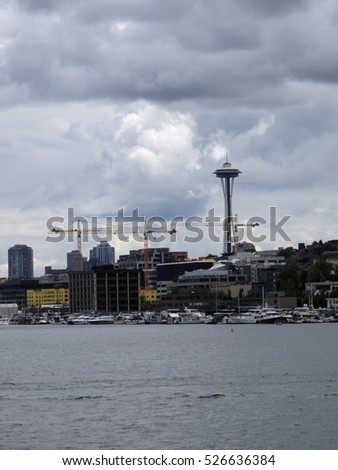 Union Lake with Downtown skyscrapers under construction and the Space Needle in the distance in Seattle, Washington, USA clouds in the sky.  June 2016.