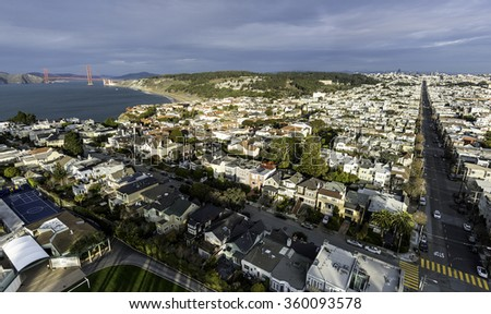 Unique aerial view from above San Francisco's Lincoln Park, looking towards the east and showing the Golden Gate Bridge, the Presidio, and downtown in the distance - stock photo