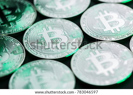 Unique bitcoin group photo. Conceptual closeup image for worldwide cryptocurrency and digital payment system. Green metallic reflections.