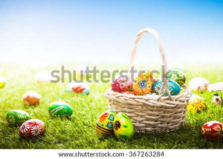 Unique hand painted Easter eggs in basket and lying on grass, blue sky. Traditional decoration in sun light - stock photo
