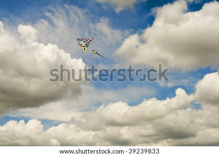 Unique Kite Flying High in Cloudscape Against Blue Sky - stock photo