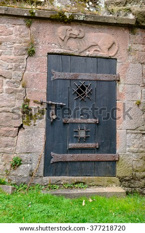 Unique old wooden door with iron plating and log underneath stone engraving of dog overhead in stone boundary wall