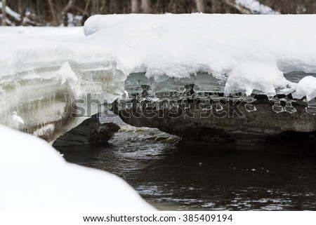 Unique ornamental ice formations hang from an snow-covered ice shelf over a flowing river in northern Wisconsin.