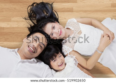 Unique perspective Asian family smiling at the camera while lying down on the wooden floor at home