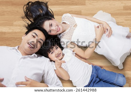 Unique perspective of happy family lying down on the wooden floor while looking at the camera - stock photo
