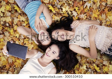 Unique perspective of three teenage girls taking picture with smartphone while lying down on autumn leaves - stock photo