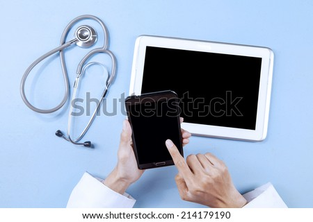 Unique Perspectives of Doctor working with smart phone and digital tablet while touching the screen - stock photo