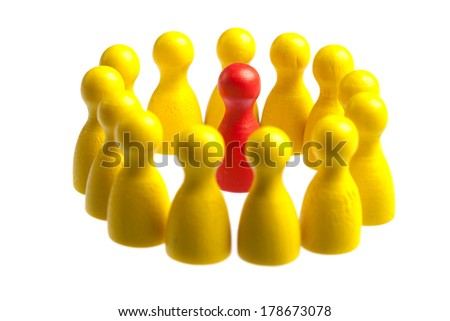 Unique red pawn centered in the middle of a large group. Concept for uniqueness, being stuck in the middle, center. Cutout, isolated on white. - stock photo