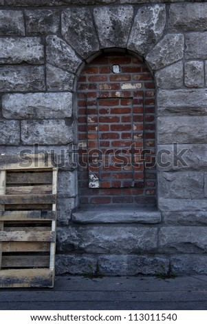 Unique shaped bricked window on rustic rock wall