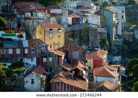 Unique view on the old town of Porto, Portugal, at sunset when one yellow vintage house catches the first sunlight of the day and stands out in the image - stock photo