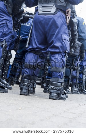 Unit of police special forces in riot gear waiting for orders. - stock photo