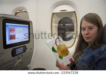 UNITED ARAB EMIRATES, EMIRATES AIRLINES FLIGHT, 27 JULY 2014 - Young woman traveler reading airplane menu card and choosing meal, Emirates airlines