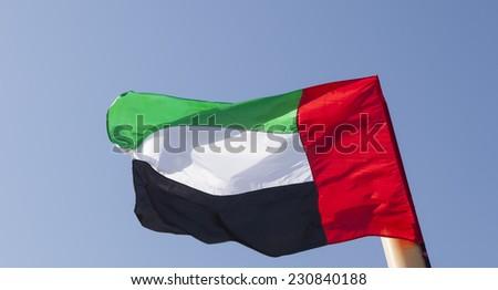 United Arab Emirates flag flying with blue sky background - stock photo