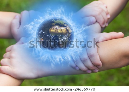 United Children's hands holding a globe outdoors. Green lawn in the background. Elements of this image furnished by NASA, - stock photo