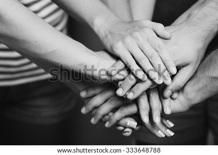 United hands close up.  Black and white retro stylization - stock photo