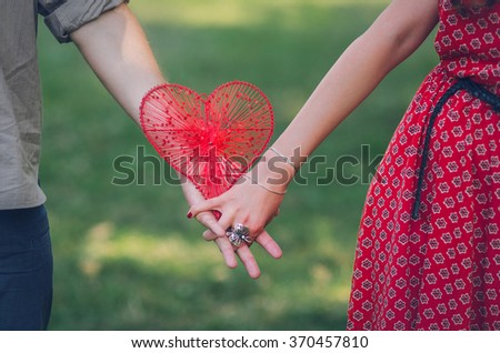 United hands of young woman and man holding a red heart. Ring on a woman's finger. Saint Valentine's day.