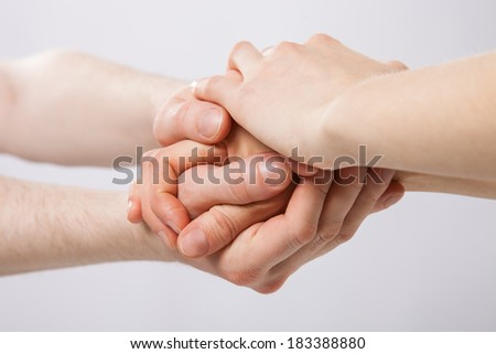 United hands on grey background - closeup shot - stock photo