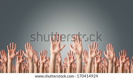 United hands raised in the air over gray background, support, surrender or voting concept.