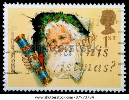 UNITED KINGDOM - CIRCA 1997: A British Used Christmas Postage Stamp showing Father Christmas and Christmas Cracker, circa 1997 - stock photo