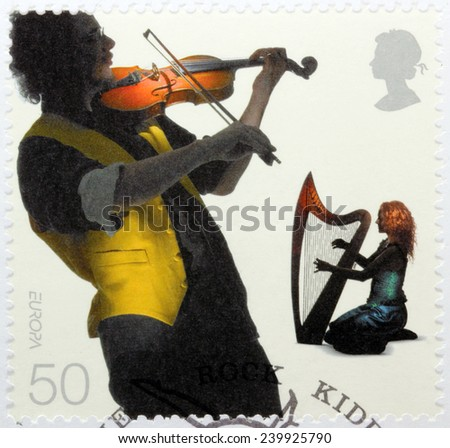 UNITED KINGDOM - CIRCA 2006: A stamp printed by GREAT BRITAIN shows two European musicians - fiddler and harpist, circa 2006 - stock photo