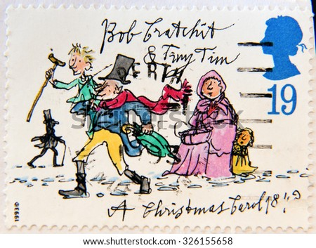 """UNITED KINGDOM - CIRCA 1993: A stamp printed in United Kingdom from the """"Christmas 150th anniversary of A Christmas Carol novel by Charles Dickens"""" shows Bob Cratchit and Tiny Tim, circa 1993.  - stock photo"""