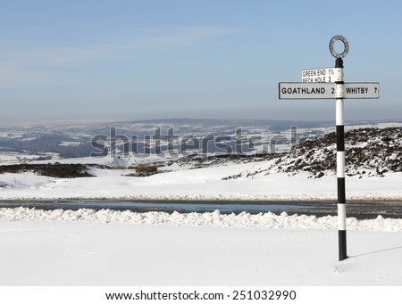 United Kingdom, Finger post, Yorks North Riding, pointing to Goathland, Beck Hole and Whitby. North Yorkshire, England, United Kingdom, North Yorkshire Moors in snowy conditions. - stock photo