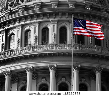 United State Capitol Building for congress with american flag flowing in breeze and columns in background - stock photo
