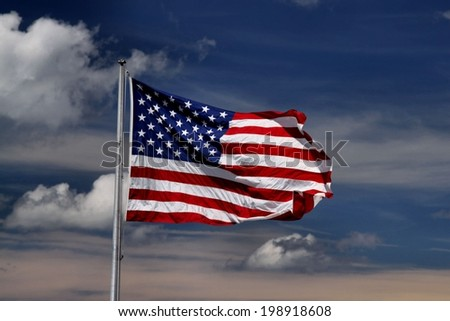 united stated flag with blue sky and white clouds