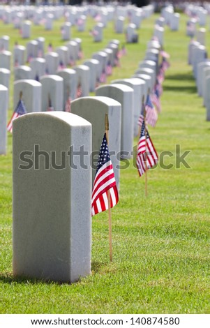 United States American Flags decorate the gravestones of veterans at a USA national cemetery on Memorial Day. - stock photo