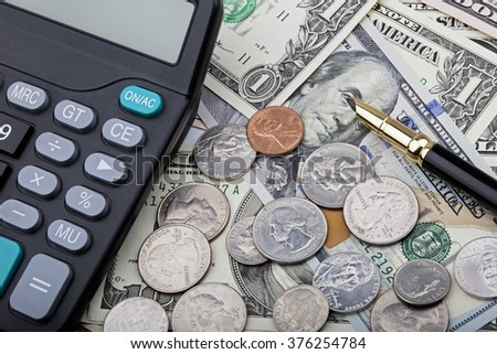 United States bank notes and coins with a calculator and pen
