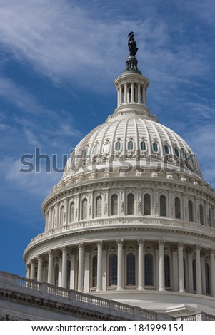 United States Capitol Building Dome against a bright blue sky with turbulent clouds