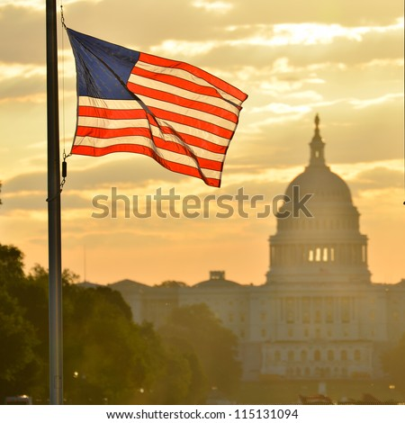 United States Capitol building silhouette and US flag at sunrise - Washington DC - stock photo
