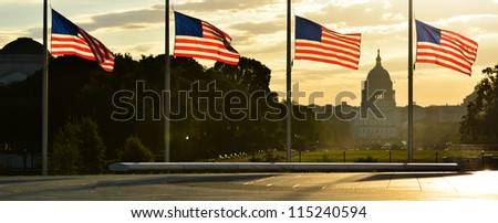 United States Capitol building silhouette and US flags around Washington Monument at sunrise - Washington DC - stock photo