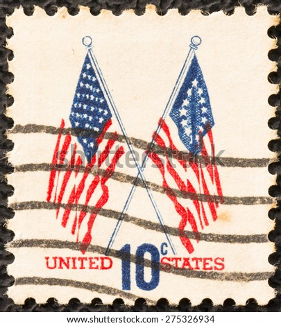 UNITED STATES - CIRCA 1973 :: A postage stamp printed in the United States, features waving US flags, circa 1973 - stock photo