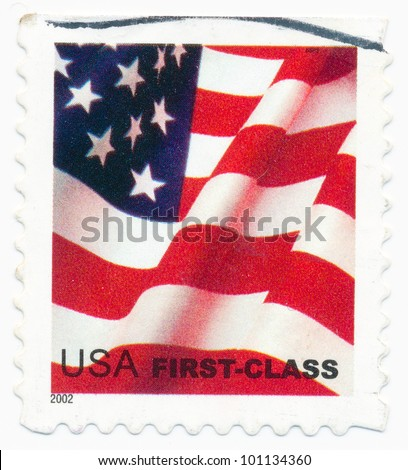 UNITED STATES - CIRCA 2002: A postage stamp printed in the United States, features waving US flag, first-class, circa 2002 - stock photo