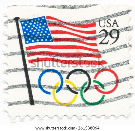 UNITED STATES - CIRCA 1991: A postage stamp printed in the United States, features waving US flag and Olympic rings, circa 1991 - stock photo