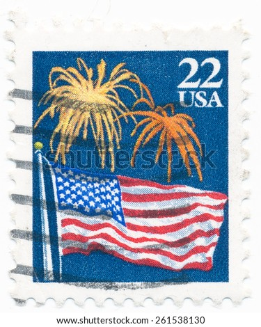 UNITED STATES - CIRCA 1987: A postage stamp printed in the United States, features waving US flag and fireworks, circa 1987 - stock photo