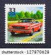 UNITED STATES - CIRCA 1999: a postage stamp printed in USA showing an image of a sixties red Ford Mustang car, circa 1999. - stock photo
