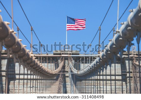 United States Flag at top of Brooklyn Bridge. There is a deep blue sky on background, on foreground there are all the wires of the bridge. Patriotism concept. - stock photo