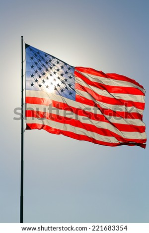 United States flag with sun as a backlight shining through - stock photo