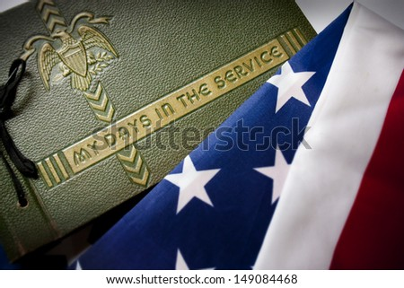 United States Memorial Day remembrance photo of a World War II  Military Service photo album with  United States Flag as a background symbolizing memories of a war veteran's military service. - stock photo