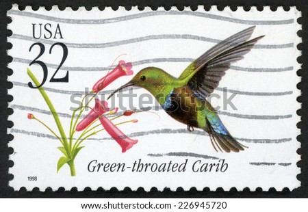 UNITED STATES OF AMERICA - CIRCA 1998: post stamp printed in USA (US) shows green throated carib bird (eulampis holosericeus, hummingbird) flying near plant; Scott 3223 A2504 32c, circa 1998 - stock photo