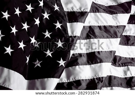 United States of America flag in black and white waving in the wind and sunlight and wind closeup - stock photo