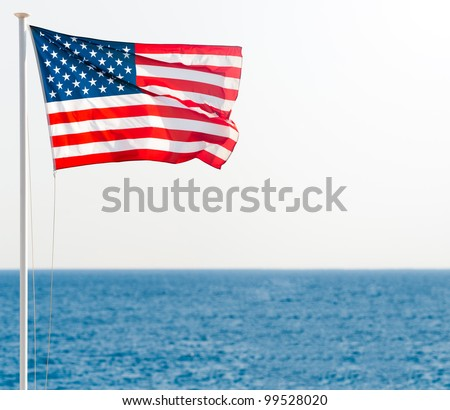 united states of america flag on pole with blue sea in background and clear sky. Lots of copy space. - stock photo