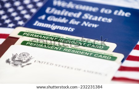 United States of America permanent resident cards, green card, with US flag on the background. Immigration concept. Closeup with shallow depth of field. - stock photo