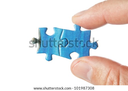 United two puzzle in the fingers. On a white background. - stock photo