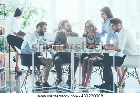 Unity is a key to success. Group of young business people working and communicating together while sitting at the office desk with colleagues sitting in the background  - stock photo
