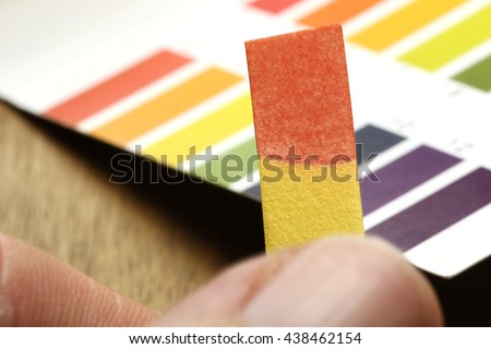 universal indicator paper with acidic testing - stock photo