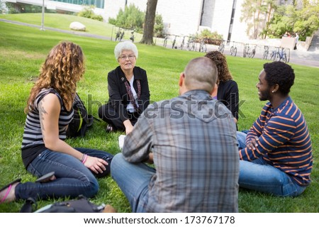 University class taking place outdoors with small group of students - stock photo