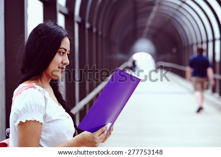 University / college student girl looking happy smiling with book on the bridge - stock photo